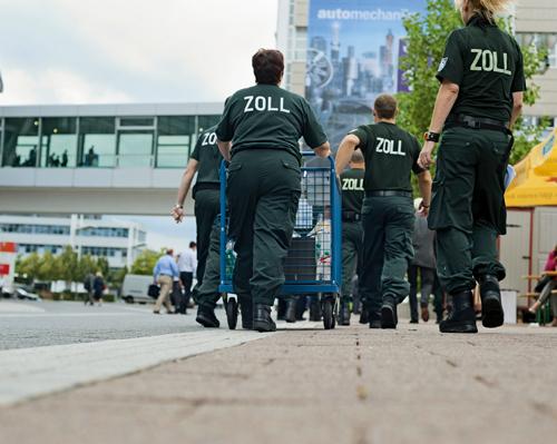 Zehn Zöllner marschieren in die Agora-Halle der Automobilzulieferermesse Automechanika in Frankfurt
