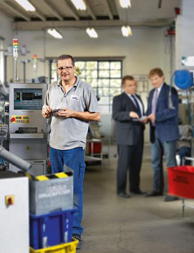Bei der Firma Schrimpf & Schöneberg in NRW schleifen 16 behinderte Mitarbeiter Metallfedern, auch Dirk Becker (li.).