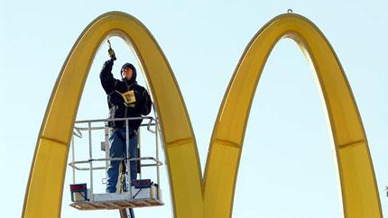 Ein Handwerker bessert den Lack an einem McDonalds Zeichen aus.