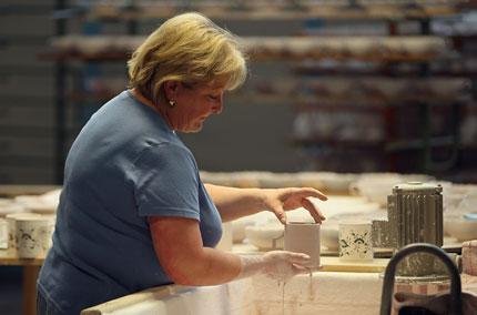 Eine Mitarbeiterin der Porzellan-Manufaktur Meissen bereitet Tassen für die Glasur vor.