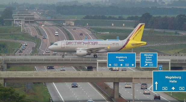 Ein Airbus A319 überquert am Flughafen Halle/Leipzig die Brücke über die Autobahn.