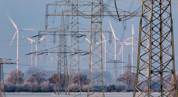 Eine Stromtrasse mit Windrädern im Hintergrund.