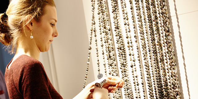 Eine Besucherin der Münchener Schmuckmesse Inhorgenta schaut sich Ketten an.