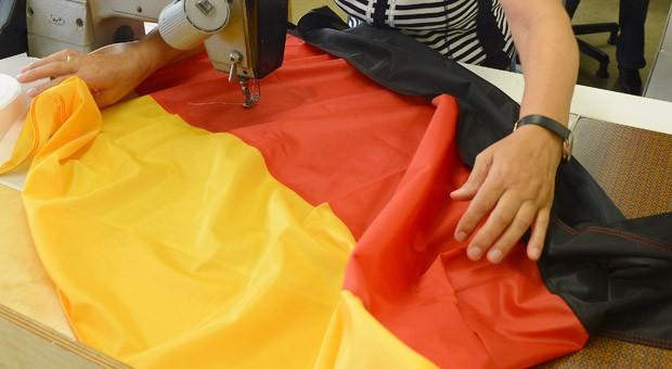 Eine Mitarbeiterin von FahnenFleck näht in Hamburg eine Deutschland-Flagge.