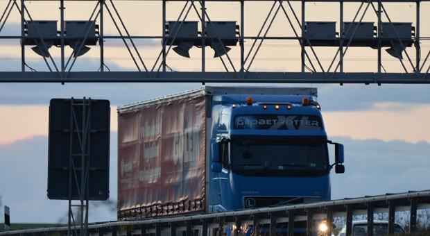 Ein LKW fährt unter einer Mautbrücke: Die nach Schadstoffausstoß gestaffelten Mautsätze sollen zum 1. Januar 2015 überwiegend sinken.