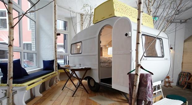 """Der 70er Jahre Wohnwagen """"Kleine Schwester"""" steht umgeben von Birken auf einem Holzpodest in der Halle."""