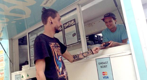 Ein Kunde zahlt seinen Lunch beim schwedischen Food Truck Bun Bun über ein mobiles Kartenterminal.
