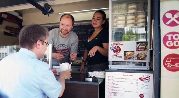 """Peter Appel mit einer Mitarbeiterin in seinem Food Truck mit dem Namen """"Swagman""""."""