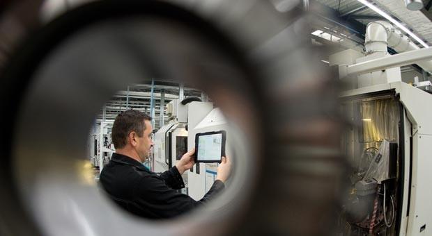 Blick durchs Zahnrad: Ein Mitarbeiter des Antriebsspezialisten Wittenstein scannt im Zahnradwerk in Fellbach (Baden-Württemberg) mit einem Tablet PC einen Barcode an einer Maschine.