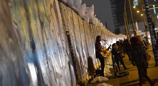 """Ein Straßenmusiker vor der East Side Gallery in Berlin: Entlang des ehemaligen Verlaufs der Berliner Mauer sind zahlreiche Ballonstelen aufgestellt sind. Die Laternen sind Teil des Projekts """"Lichtgrenze 2014"""" zum 25. Jahrestag des Mauerfalls am 09.11.2014."""