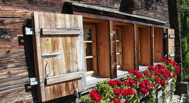 Typisches Fenster mit Blumen in den Schweizer Bergen.