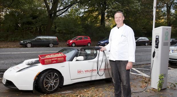 Bäcker Thomas Effenberger vor seinem Elektroauto, mit dem er Brötchen ausfährt.