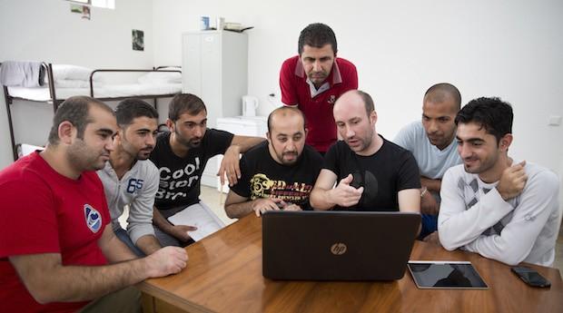 Nachhilfe: Unternehmer Sven Noack (3. v. r.) kaufte den Flüchtlingen Laptops. Hussam (2. v. r.) und die anderen mussten aus ihrer Heimat fliehen, weil sie politisch oder religiös verfolgt wurden. Aus Furcht, entdeckt zu werden, wollen die meisten nur ihre Vornamen nennen.