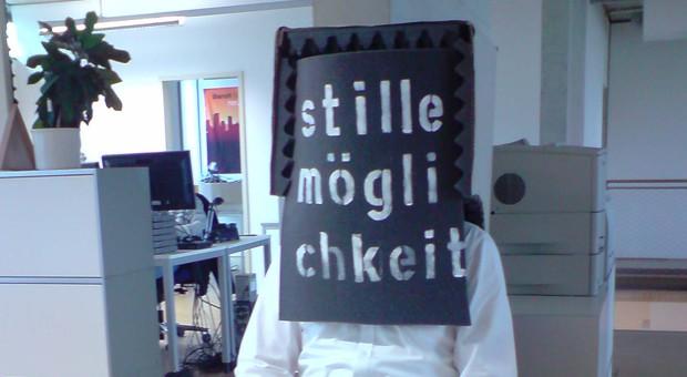"""Eine der Kunstaktionen greift einen Wunsch der Mitarbeitern auf: mehr Ruhe im Großraum. Künstler Walbrodt klebte dafür dem Geschäftsführer einen speziellen Akustikschaumstoff mit der Aufschrift """"Stille Möglichkeit"""" auf den Kopf."""