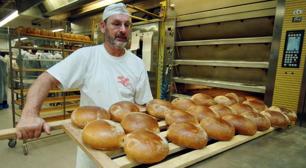 Der Bäcker Armin Balzuweit von der Bäckerei Sailer in Stuttgart nimmt  ein Brett mit Broten aus dem Backofen.
