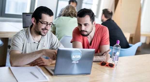 """Zwei  """"ChancenNutzer"""": Bogdan Obretemov (links) und Murat Serbes arbeiten im Social Impact Lab an ihrer Handy-App für Gastronomen."""