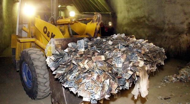 Ein Schaufelbagger transportiert in einem unterirdischen Stollen bei Halberstadt altes DDR-Geld.