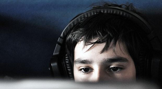 Teenager mit Kopfhörern am Computer: Eltern müssen ihre Kinder über Filesharing aufklären.