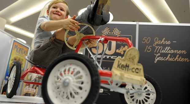 Mit Gefährten wie diesem fing alles an: Der kleine Finn sitzt während einer Spielwarenmesse im Jahr 2012 auf einem historischen Kettcar-Modell. Jetzt hat Hersteller Kettler Insolvenz angemeldet.