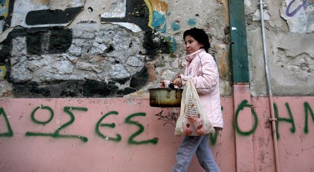 Eine junge Frau trägt einen Topf mit Essen aus einer Suppenküche in Athen.