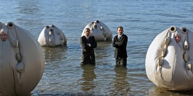 """Andy Bichlbaum und Mike Bonanno (v.l.n.r) stellen im Film """"die Yes Men - Jetzt wird's persönlich """"den Survivaball vor, der Manager vor Klimakatastrophen schützen soll."""