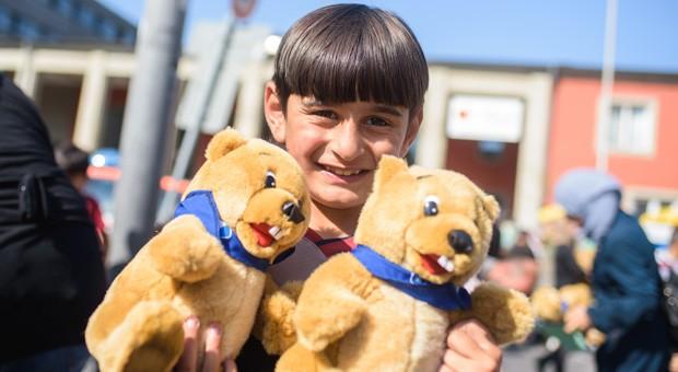 Die Bereitschaft, Flüchtlingen zu helfen, ist in Deutschland vielerorts groß. Auf unserem Foto freut sich ein Flüchtlingskind am Münchener Hauptbahnhof über geschenkte Stofftiere.