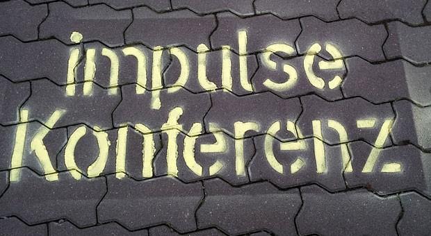 Eine Kreideschablone weist den Teilnehmern den Weg zur impulse-Konferenz.