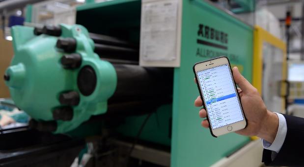 Mit dem Smartphone überwacht Geschäftsführer Thomas Dreusicke der Firma India Deusicke die Maschinen in der Fertigungshalle.