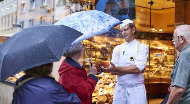 Diese Uniform ist sein Markenzeichen: Bäcker Josef Hinkel begrüßt Kunden vor seinem Geschäft in Düsseldorf - unverwechselbar mit weißer Bäckerkluft, kombiniert mit Hosenträgern.