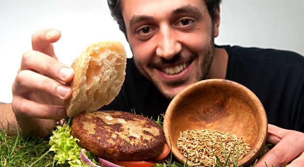 """Insekten essen für Einsteiger: Co-Gründer Baris Özel mit einem Insekten-Burger von von """"Bugfoundation""""."""