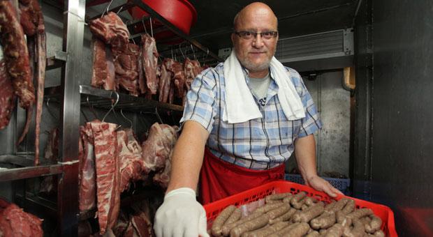 Rolf Lanzinger zeigt in der Kühlkammer seiner Fabrik in Phnom Penh einer seiner Bestseller: eine Bratwurst nach deutscher Art.