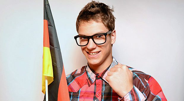 Die Fahne verrät's: Dieser junge Mann ist ein Fußballfan. Ob er bei der Fußball-EM am Arbeitsplatz jubeln darf? Das regelt nicht nur das Arbeitsrecht; es kommt auch auf sein Verhältnis zum Chef an.