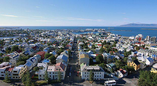 Bunte Dächer am Wasserrand - und Schnee auf den Bergen am Horizont - Reykjavík ist aufgeräumt und liegt mitten in einer Landschaft wilder Schönheit.