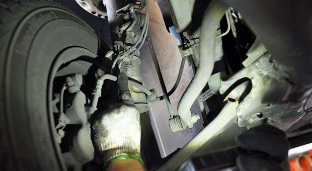 Licht ins Dunkel: Bei einer Inspektion nehmen die Werkstätten anhand eines Prüfplanes die Autotechnik unter die Lupe, hier etwa die Bremsleitungen. Dafür muss das Auto aber nicht zwangsläufig in eine Markenwerkstatt.