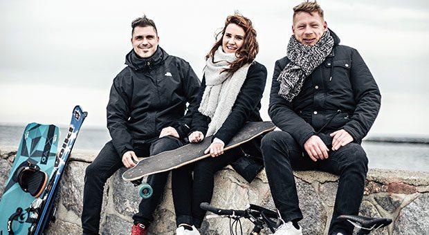Alexander Hornung, Hanna Bachmann und Christian Range (r.) bieten mit ihrem Portal Hepster Spezialversicherungen an. Auch die Sportgeräte, mit denen die Rostocker an den Warnemünder Strand gekommen sind, soll ihre Lifestyle-Versicherung schützen.