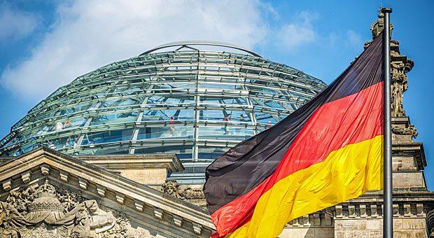 Deutsche Flagge vor dem Reichstag in Berlin: Hier muss sich die Große Koalition die Zustimmung des Parlaments für ihre Pläne abholen; erst dann kann Gesetz werden, was Union und SPD im Koalitionsvertrag vereinbart haben.